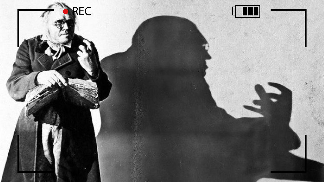 The character Dr. Caligari and his eerie shadow on a wall. This is a still from the movie.